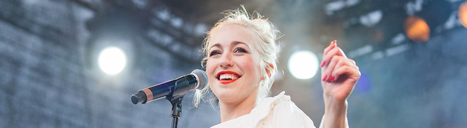 Eine Sängerin mit blonden Haaren steht auf der Bühne. Sie lacht.