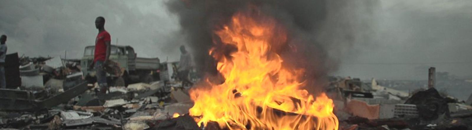 Szene aus einem Video. Auf einer Müllhalde brennt ein Feuer, die Luft ist grau, im Hintergrund stehen Männer.