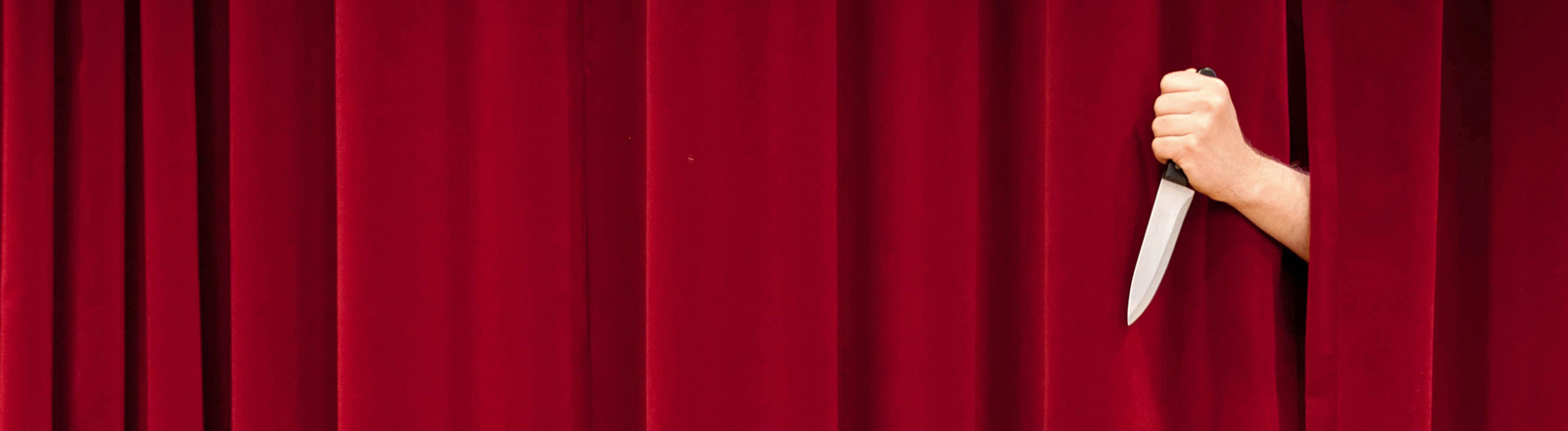 Zwischen einem roten Vorhang schiebt sich eine Hand durch, die ein Messer hält.