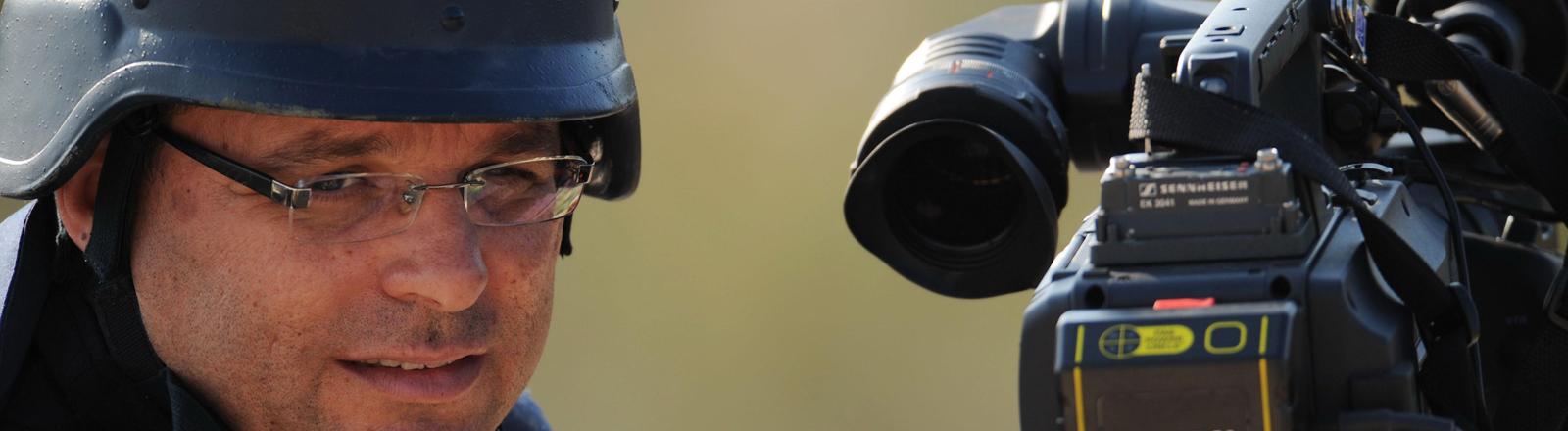 Ein Journalist berichtet aus dem Gaza-Streifen mit Helm und kugelsicherer Weste.