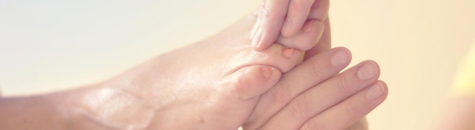 Zwei Hände massieren einen Fuß