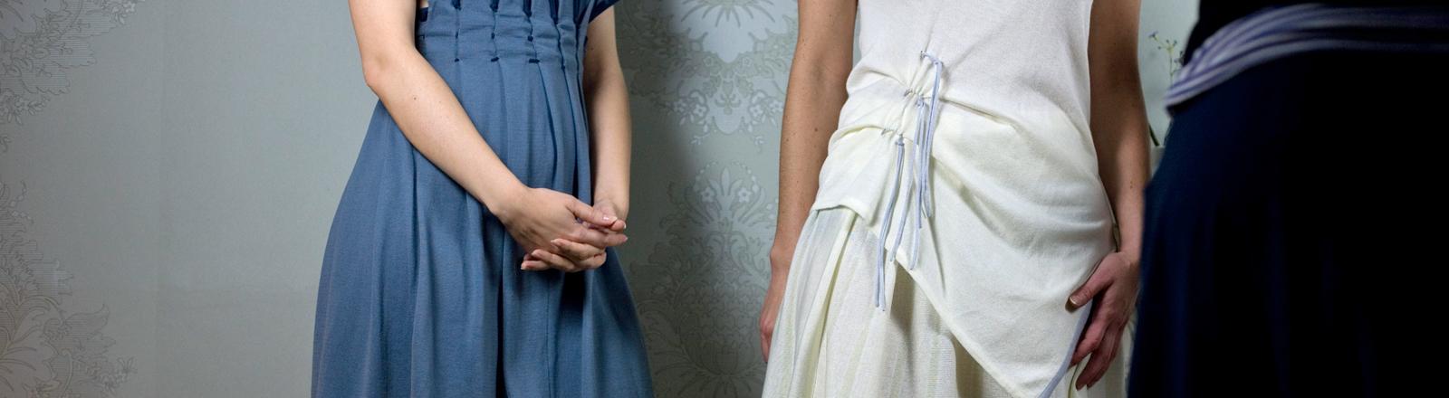 Drei Frauen in schönen Kleidern stehen nebeneinander.
