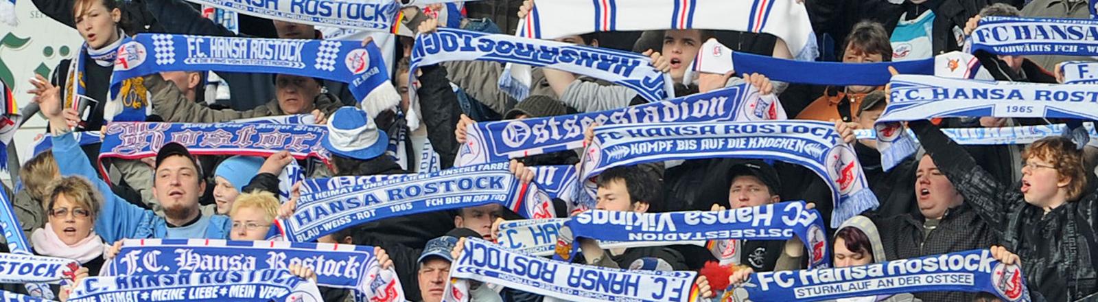 Fans von Hansa Rostock halten ihre blau-weißen Schals in die Luft; Bild: dpa