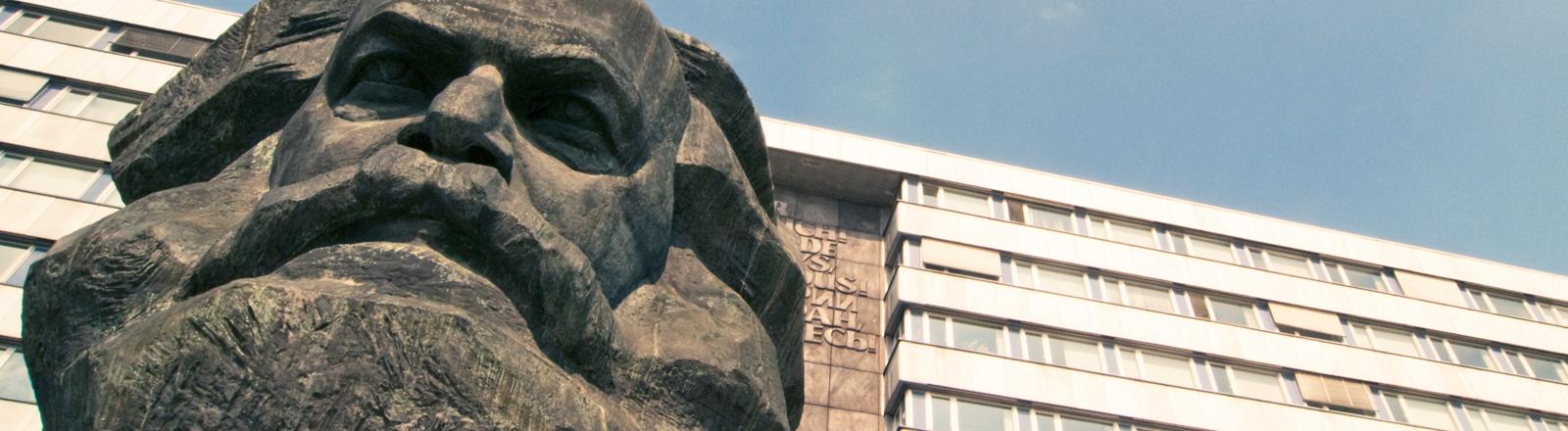 Vor einem Plattenbau steht die Büste von Karl Marx.