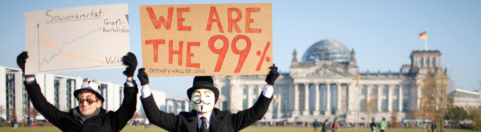 """Zwei Demonstranten halten Schilder mit der Aufschrift """"We are the 99%"""" und einer Grafik mit Kapitalismuskritik in die Luft. Im Hintergrund ist der Bundestag zu sehen; Bild: dpa"""