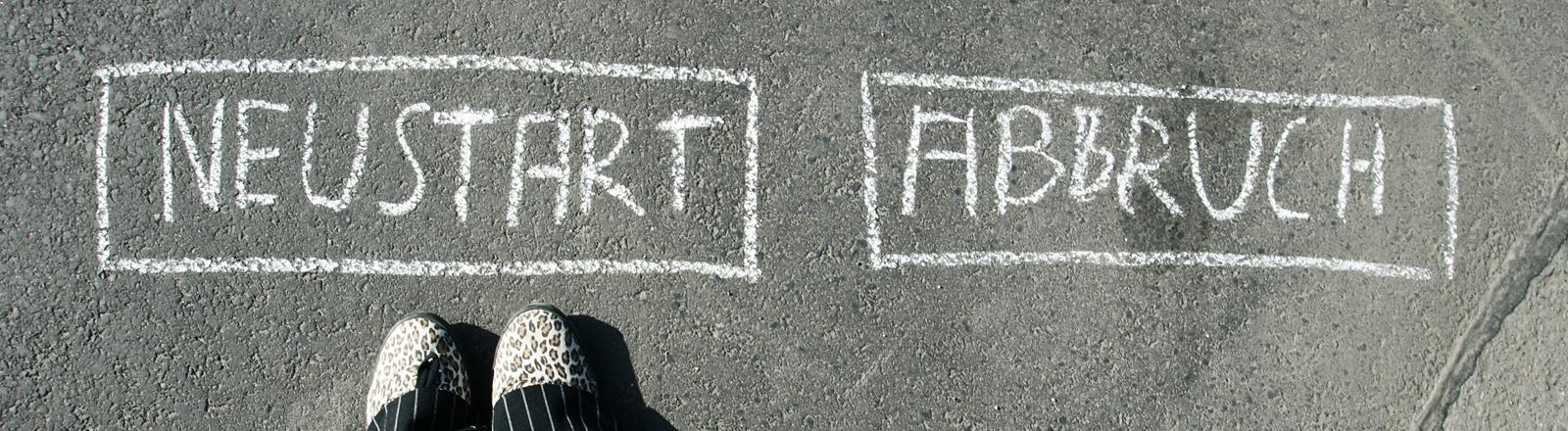 """Mit Kreide steht auf dem Boden Neustart und Abbruch, beide Worte mit einem Viereck umrandet. Vor """"Neustart"""" sind zwei Füße zu sehen."""