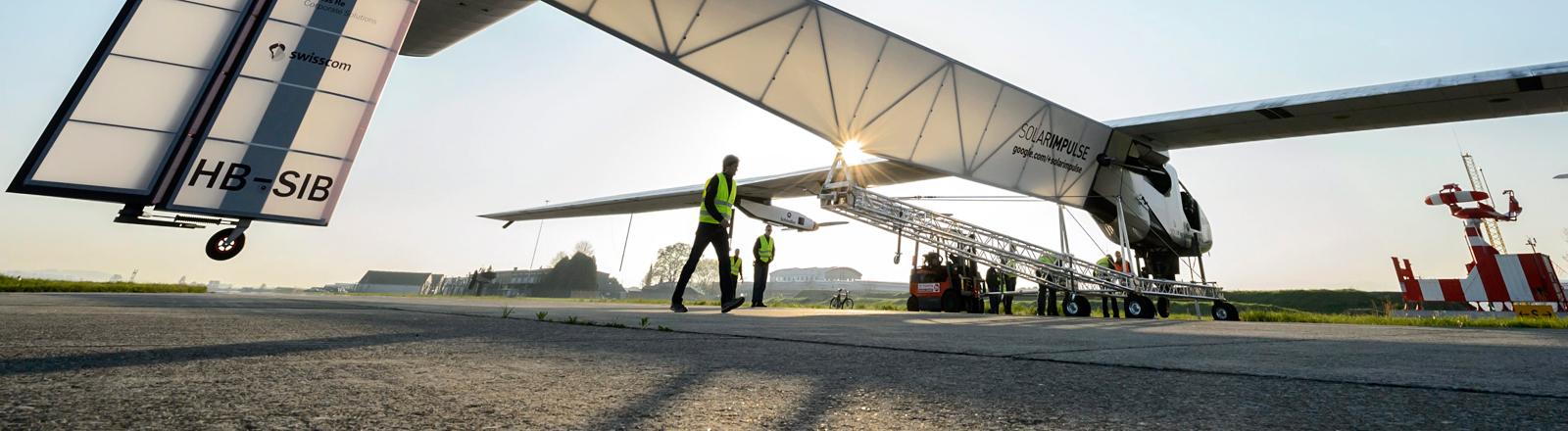 Das Solarflugzeug steht am Flughafen, die Sonne scheint durch die Rumpf hindurch, Techniker laufen herum; Bild: dpa