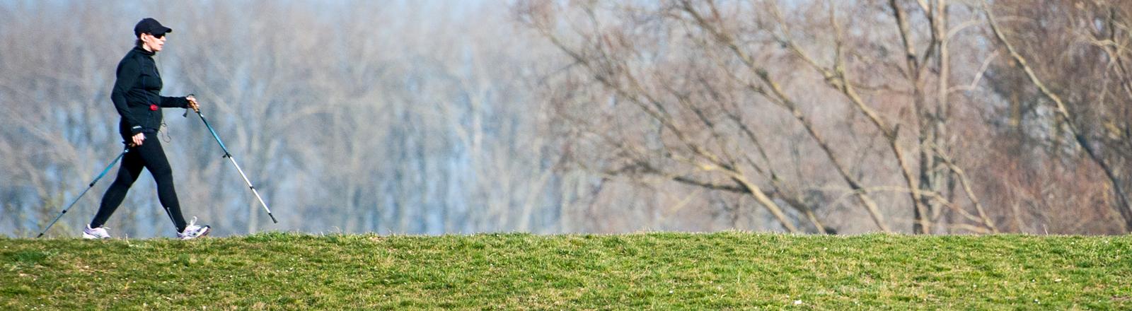 Eine Frau in schwarzer Trainingskleidung und Stöcken läuft über einen Deich; Bild: dpa