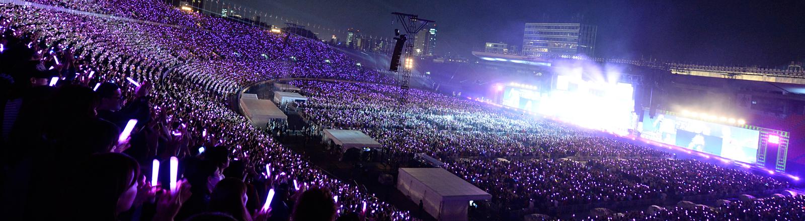 Blick in ein Stadion mit tausenden von Menschen. Viele halten Leuchtstäbe in den Händen. Auf der Bühne flackern Lichter und Leinwände.
