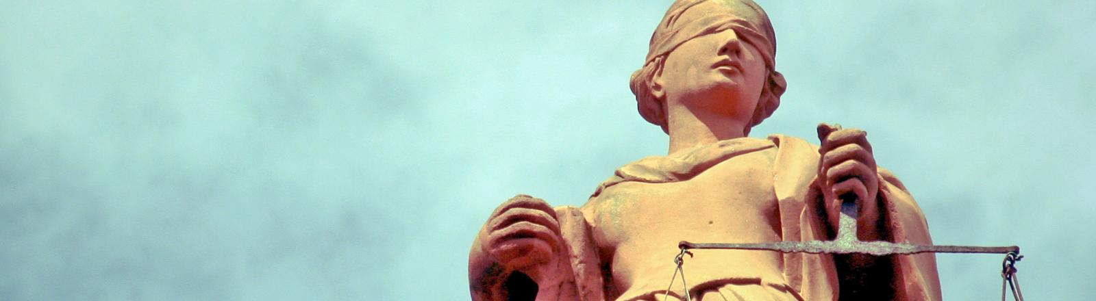 Skulptur der Justitia, eine Frau mit verbundenen Augen, in den Händen hält sie den Griff einer Waage. Die Waagschalen sind nicht zu sehen.