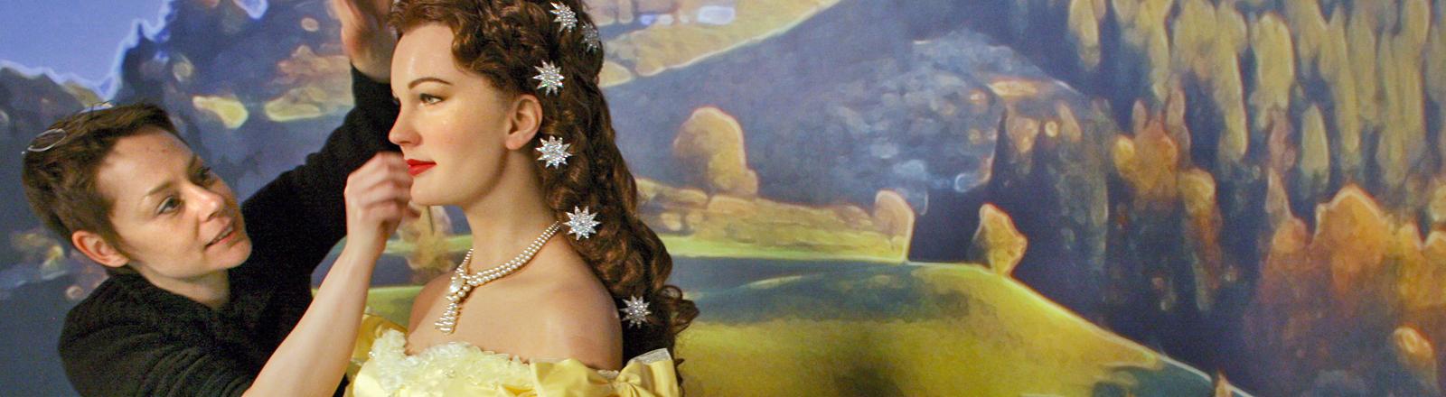 Eine Frau legt noch Hand an an einer Wachsfigur, die Romy Schneider als Königin Sissi darstellt; Bild: dpa