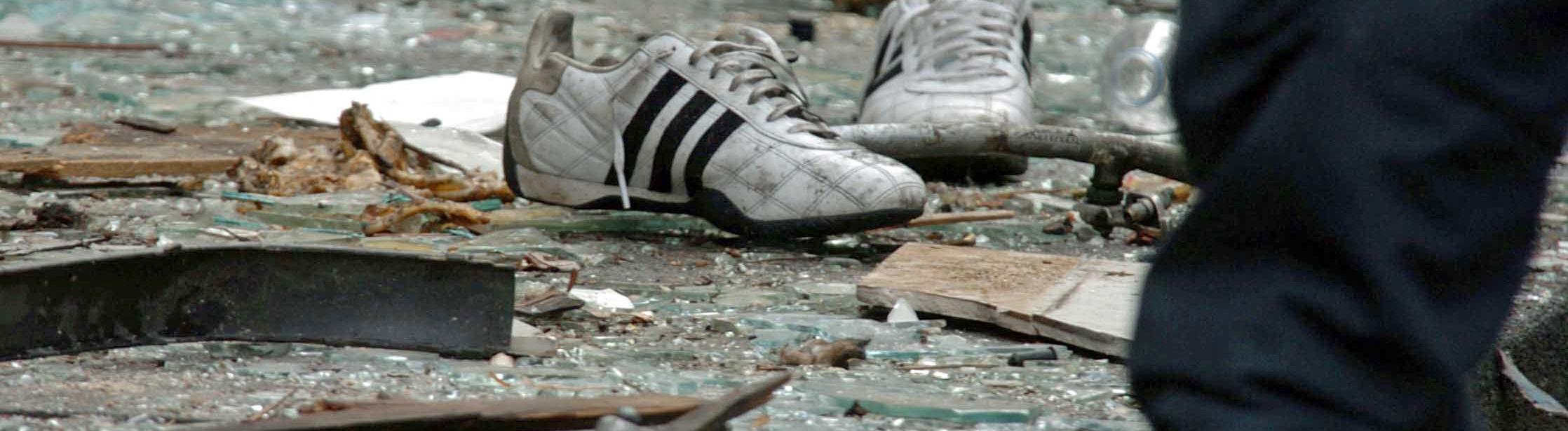 Auf dem Boden liegt ein paar Turnschuhe, ebenso viele Glasscherben und Teile von Gegenständen, die nicht zuzuordnen sind; Bild: dpa