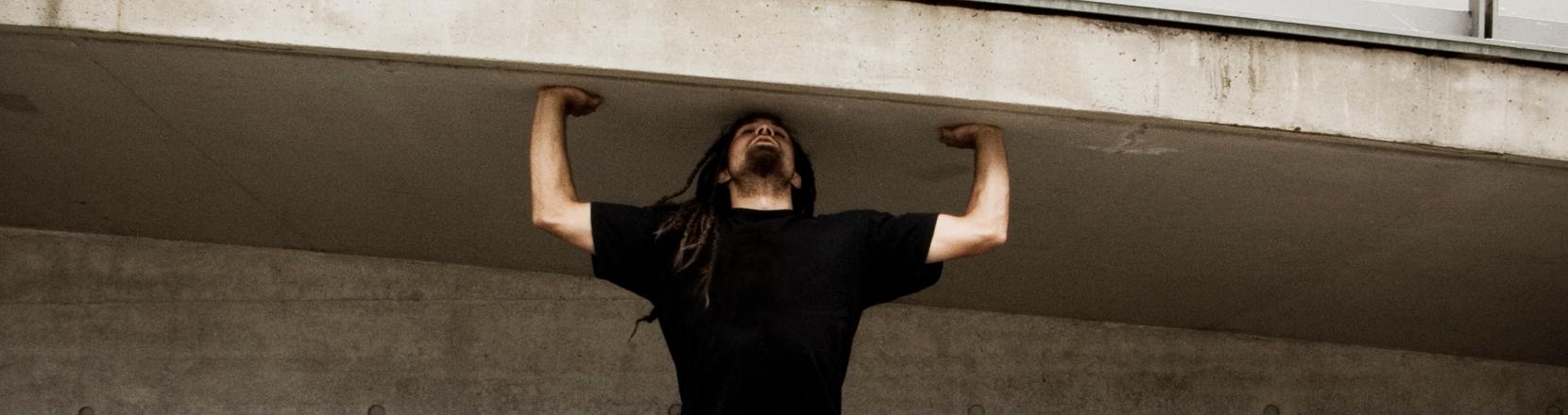 Ein Mann tut so, als könnt er er ein Treppenaufgang auf seinen Armen halten.