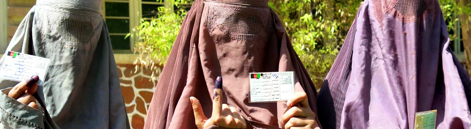 Drei afghanische Frauen zeigen ihre Wahlregistrierung und den gefärbten Zeigefinger nach Abgabe ihrer Stimme am 14. Juni 2014.