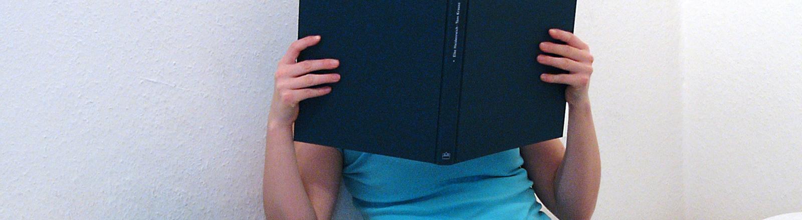 Eine junge Frau hält sich ein aufgeschlagenes Buch vors Gesicht