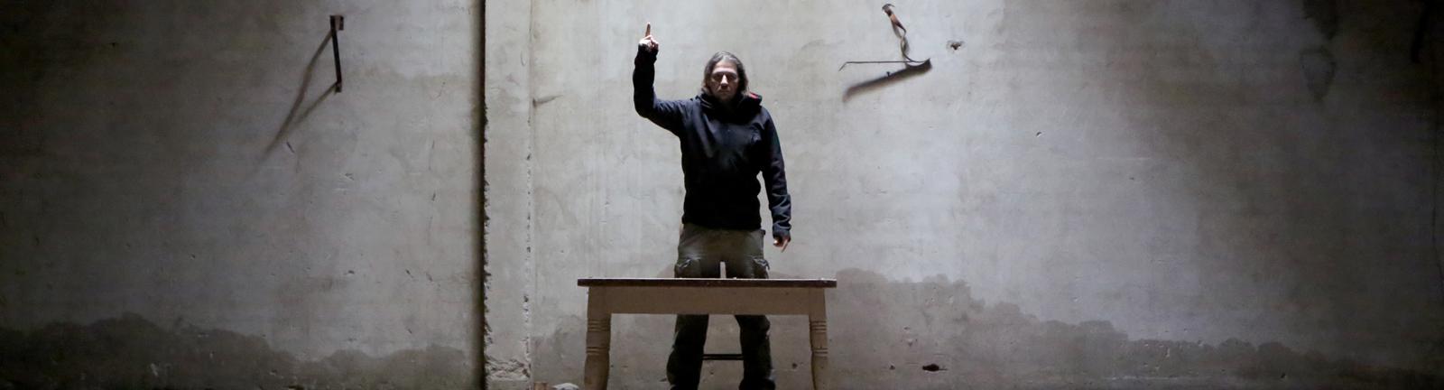 Ein Mann steht vor einem Tisch und hält eine Rede