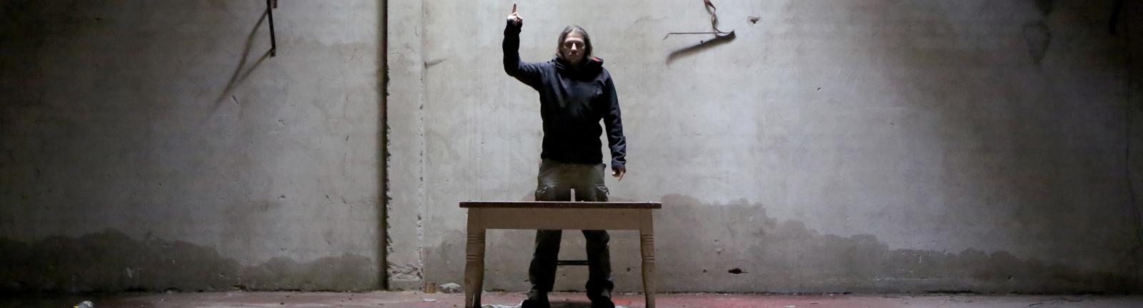 Ein Mann steht vor einem Tisch und hebt die Hand