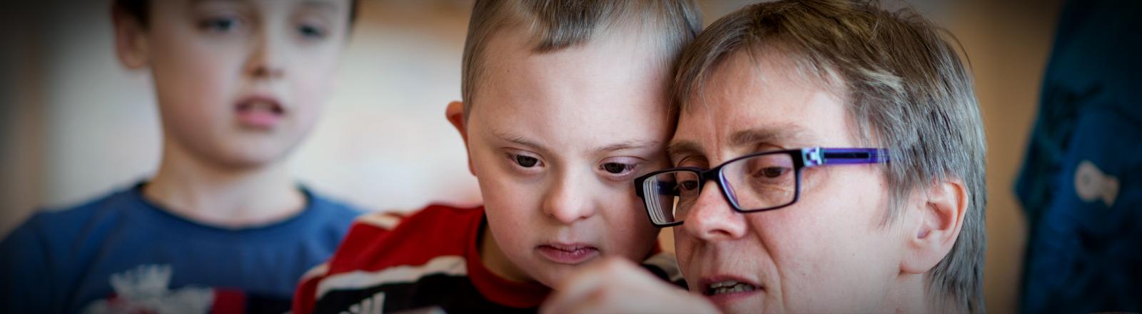 Henri, ein Kind mit Down-Syndrom, betrachtet mit seiner Mutter Fotos auf einer Digitalkamera.