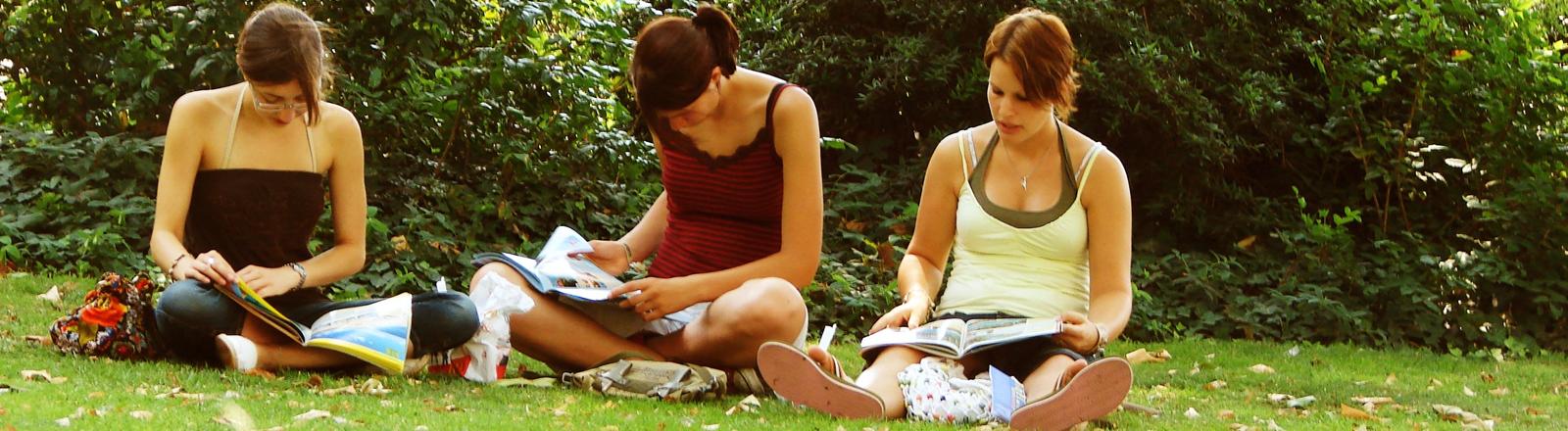 Studentinnen lesen Zeitschriften auf einer Wiese.