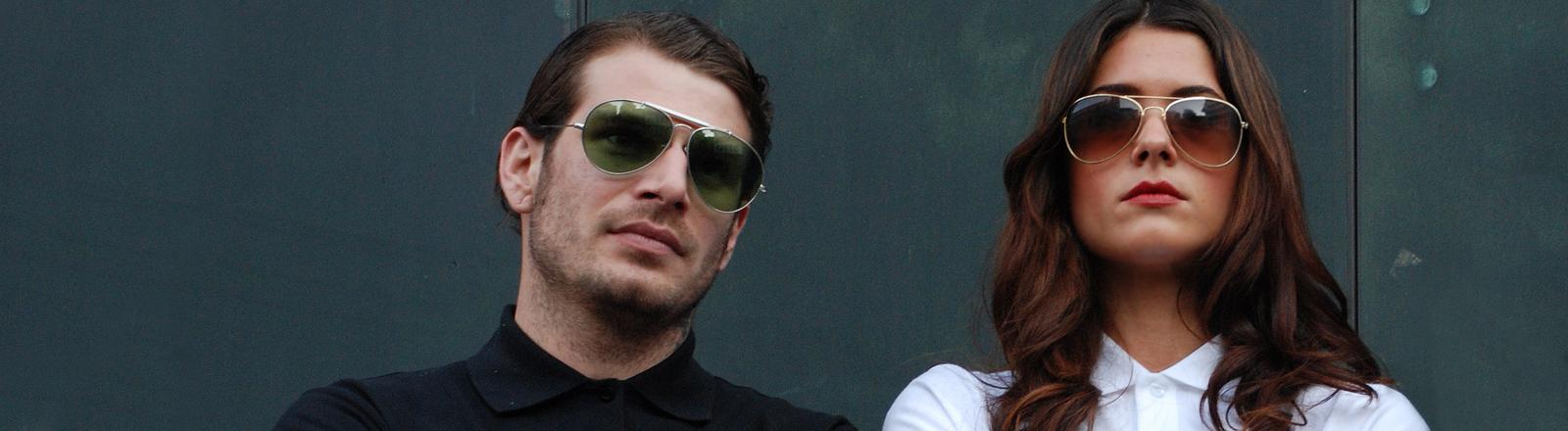 Eine Frau und ein Mann stehen provokant mit verschränkten, tätowierten Armen da und tragen Sonnenbrillen.