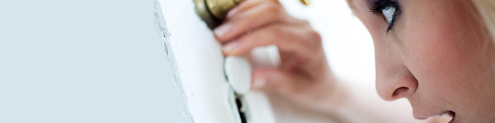Eine Frau spinkst durch ein Schlüsselloch.