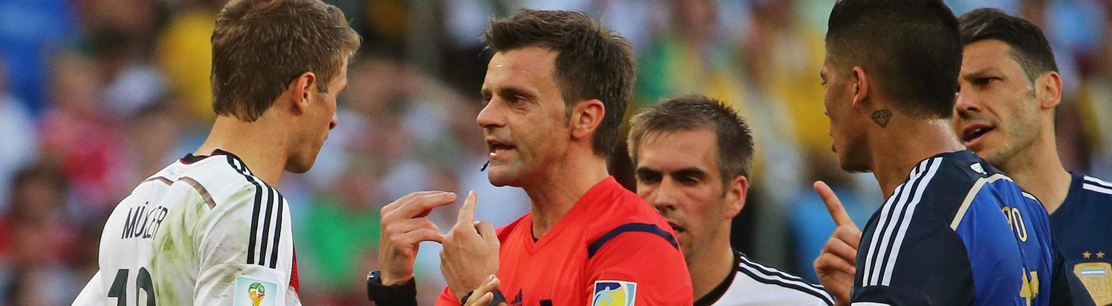 Der Schiedsrichter Nicola Rizzoli ist umgeben von vier Spielern, unter anderem Müller; Bild: dpa