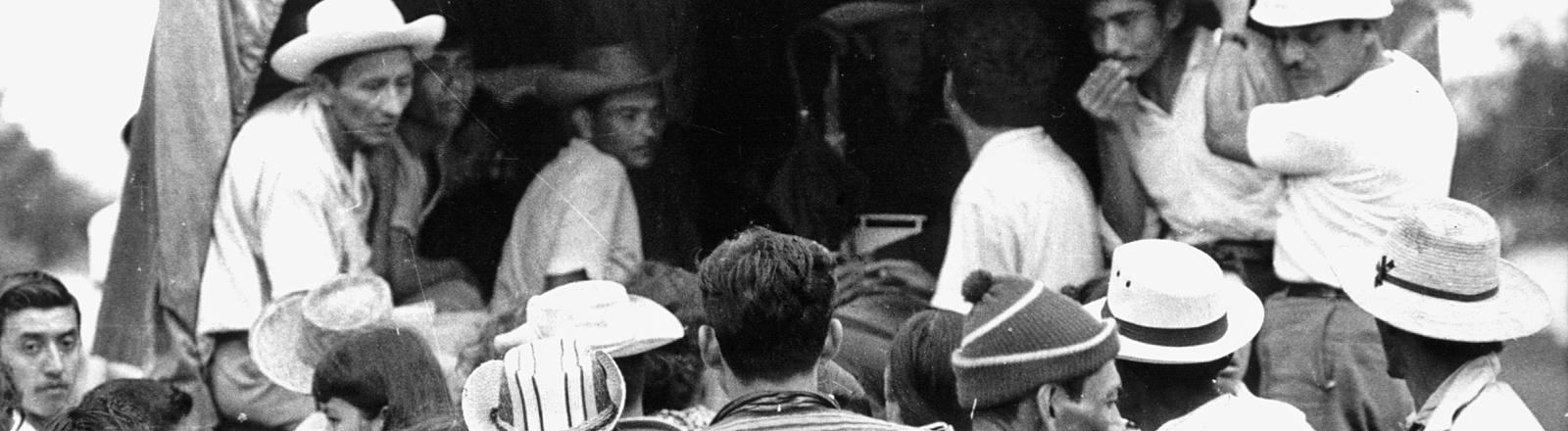 Schwarz-Weiß-Foto; vor der Rückseite eines geöffneten Lastwagen stehen mehrere Männer, auf der Ladefläche sitzen und stehen weitere Männer; Bild: dpa