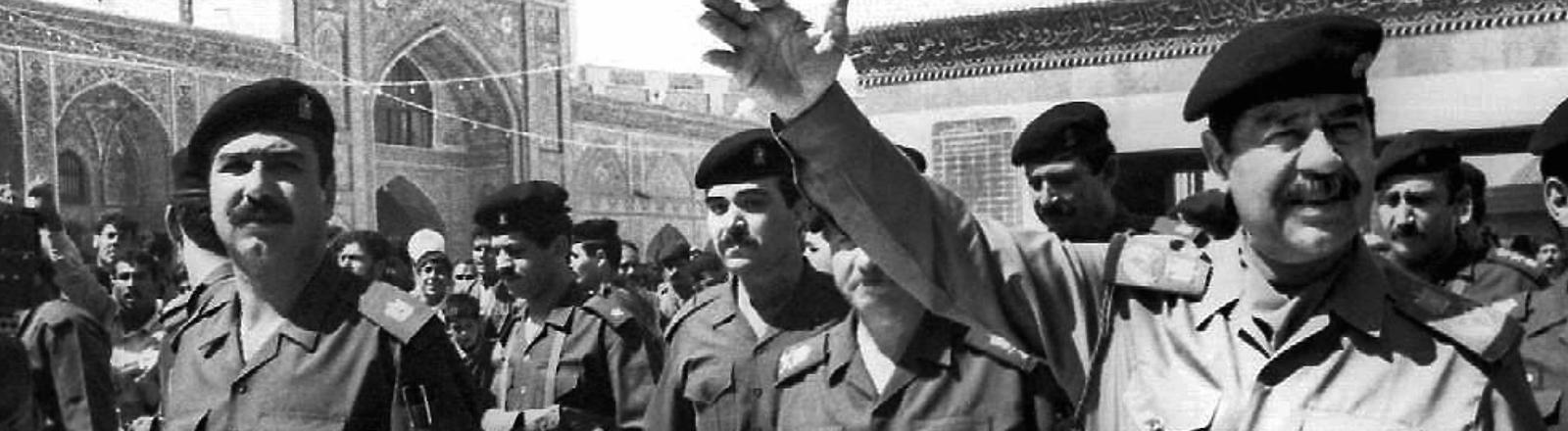 Schwarz-Weiß-Foto, Saddam Hussein in Uniform umgeben von uniformierten Männern, er streckt die rechte Hand in die Höhe; Bild: dpa
