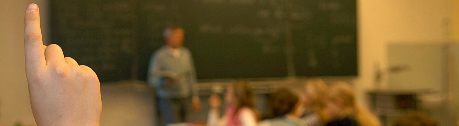 Blick in ein Klassenzimmer. Ein Lehrer steht vor der Tafel, eine Hand mit ausgestrecktem Zeigefinger ragt im Vordergrund ins Bild; Bild: dpa