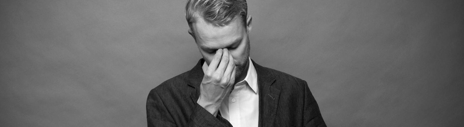 Schwarz-Weiß-Foto, ein Mann in Hemd und Jacket blickt nach unten, seine rechte Hand liegt auf seiner Nasenwurzel, nur Kopf und Oberkörper sind zu sehen.
