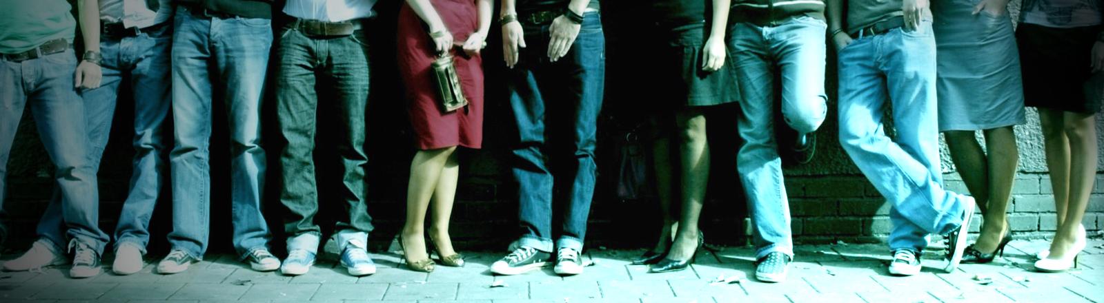 Männer in Jeans und Frauen in Röcken stehen nebeneinander an eine Wand gelehnt. Es sind nur die Beine zu sehen.
