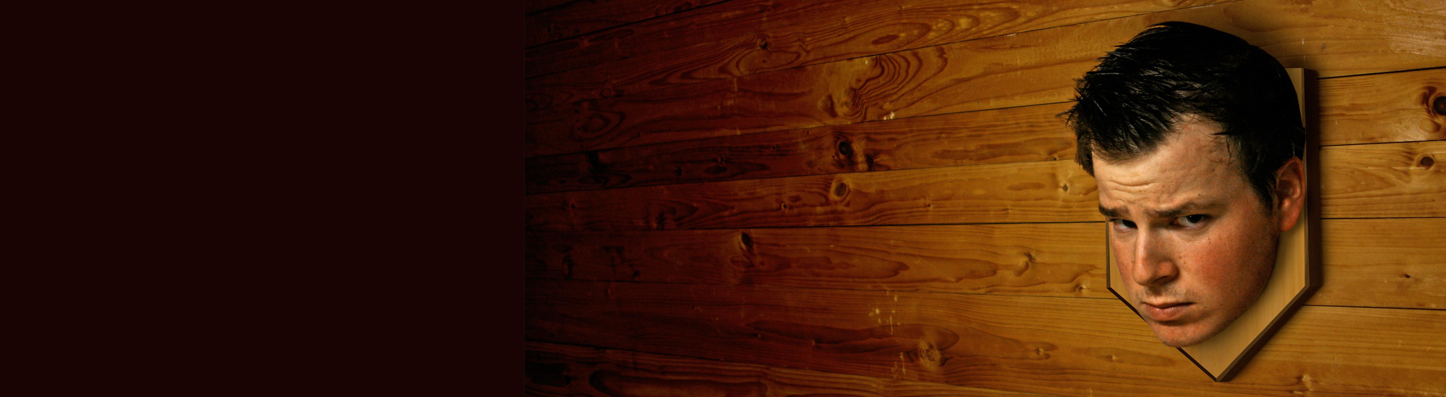 An einer Holzwand hängt der Kopf eines Mannes, ähnlich einer Trophäe. Der Mann blickt genervt.