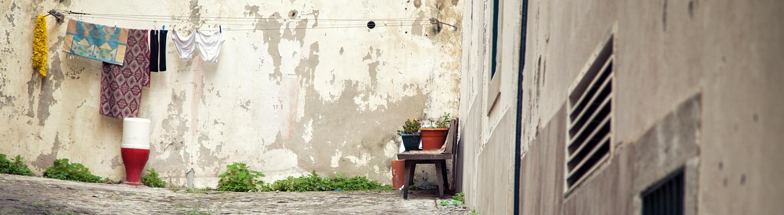 Blick in einen Innenhof. Rechts steht eine Bank mit Blumenkübeln darauf. An der hinteren Wand trocknet Wäsche auf einer Wäscheleine.