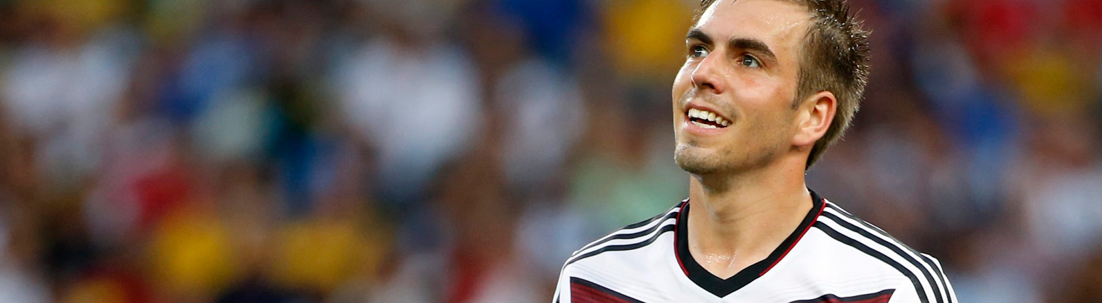 Philipp Lahm im Stadion, im Hintergrund ist unscharf das Publikum zu erkennen, Lahm lacht und blickt in die Luft; Szene aus dem WM-Finale 2014; Bild: dpa