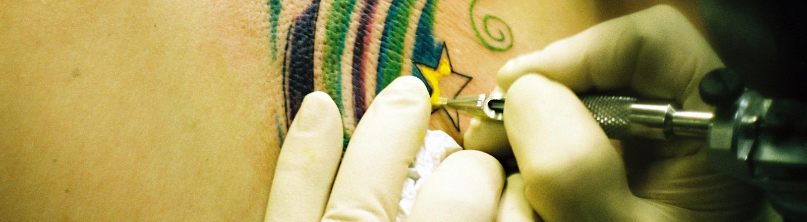 Zwei Hände in Handschuhen halten eine Tätowiermaschine an einen Rücken, ein Stern wird gelb gefärbt.