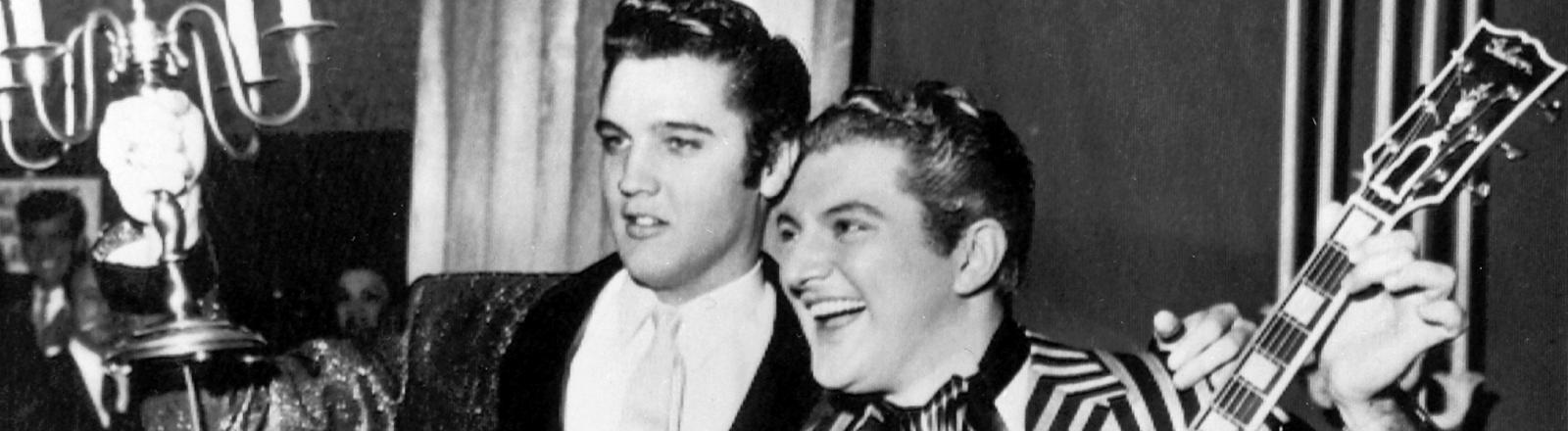 Schwarz-Weiß-Foto, Elvis Presley umarmt den Entertainer Liberace, in der anderen Hand hält er eine Lampe; Bild: dpa