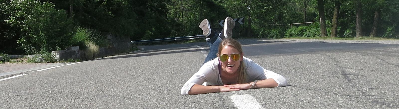Felicia Hargarten liegt auf dem Mittelstreifen eine Straße und lacht. Sie trägt eine Sonnenbrille.
