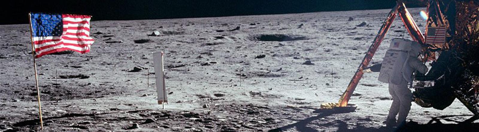 Aufnahme der Mondlandung vom 20. Juli 1969 (US-Zeit), links flaggt die US-Fahne, rechts steht ein Astronaut außen an der Landefähre; Bild: dpa