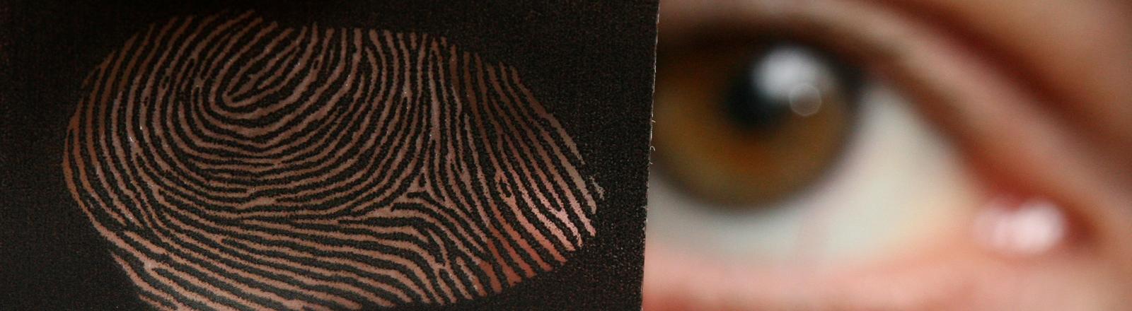 Eine Person hält das Modell eines Fingerabdrucks neben ihr Auge.