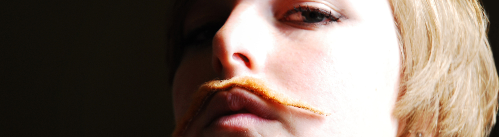 Eine junge Frau trägt einen angeklebten Schnurrbart.