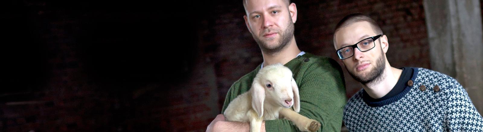 Jakob und Bene von der Band Schlachthofbronx stehen auf einem Pressefoto mit Schäfchen nebeneinander.