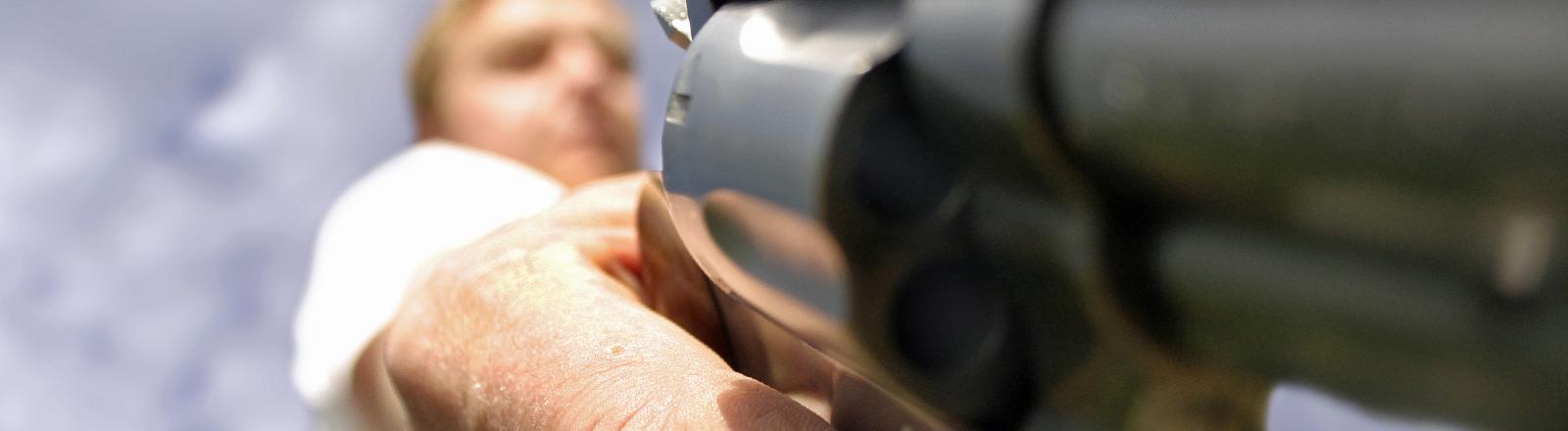 Ein Mann hält einen Revolver drohend in der Hand.