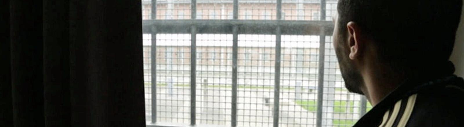 """Eine Szene aus der WDR-Dokumentation """"Moscheebau hinter Gittern"""": Ein Mann schaut durch ein Gitterfenster."""