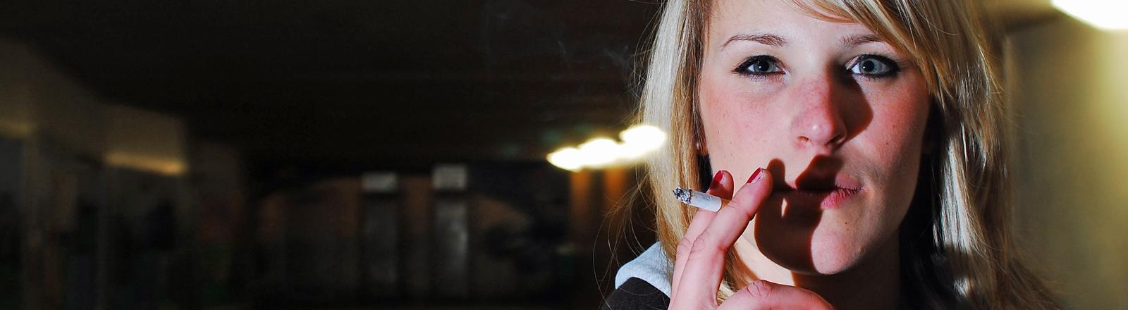 Eine junge Frau steht in einer dunklen Halle und raucht.