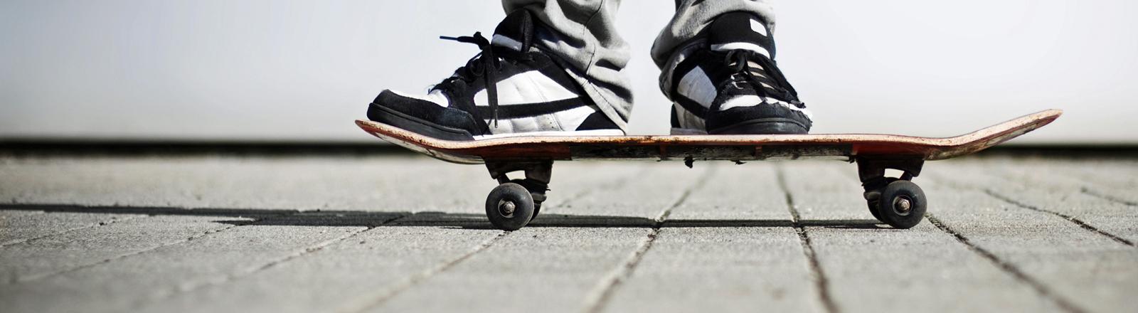 Ein Mann steht auf einem Skateboard.