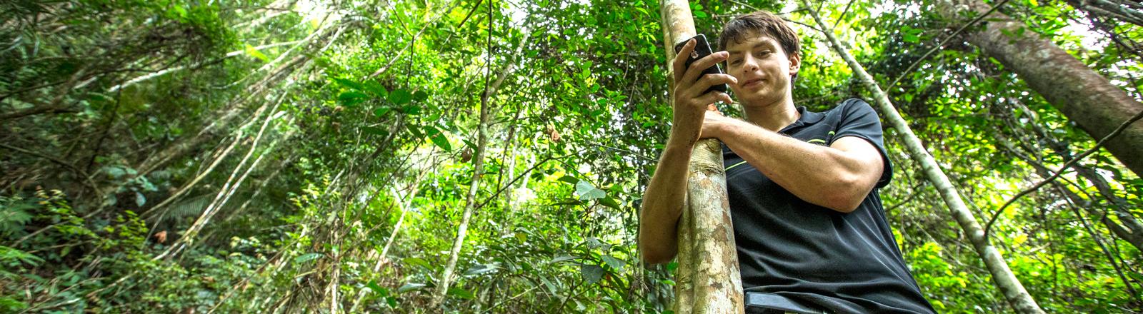 Topher White steht mit Handy im Regenwald