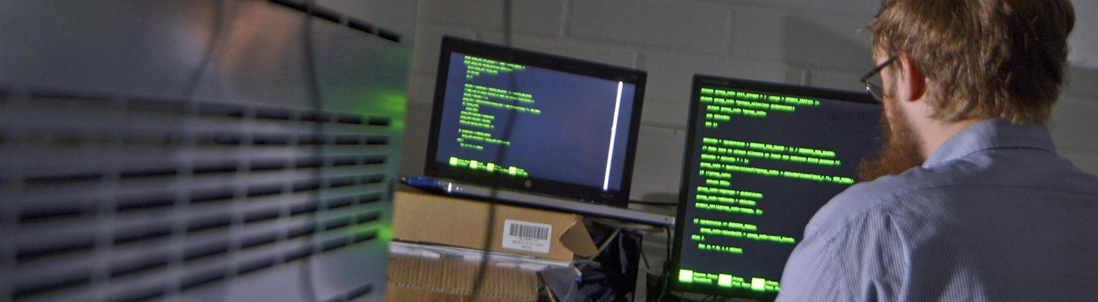 Ein Mann arbeitet in einem Serverraum an einem Computer und tippt so vor sich hin.