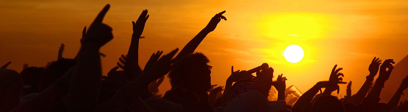 Jugendliche recken bei einem Festibal ihre Arme der Sonne entgegen.