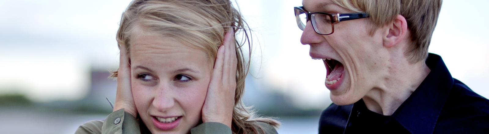 Eine Frau links im Bild hält sich die Ohren zu. Rechts neben ihre steht ein Mann, der sie anschreit.
