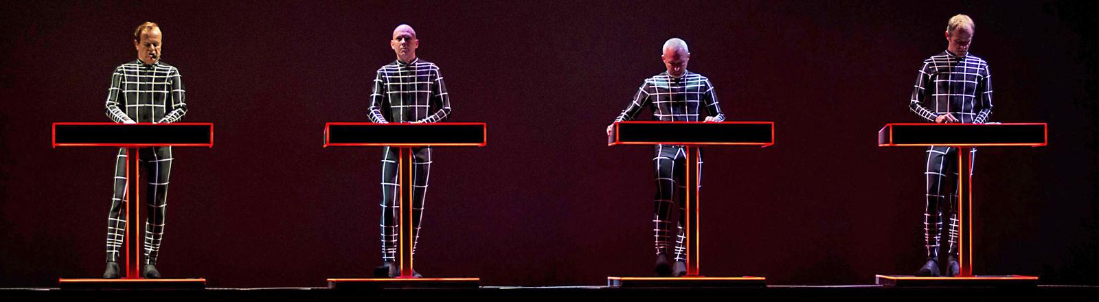 Die vier Bandmitglieder von Kraftwerk stehen auf der Bühne nebeneinander hinter Konsolen; Bild: dpa